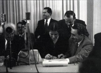 Golda Meir unterzeichnet die Unabhängigkeitserklärung von 1948. Links Ben Gurion. Foto Benno Rothenberg - http://www.archives.gov.il/, Public Domain, https://commons.wikimedia.org/w/index.php?curid=48441234