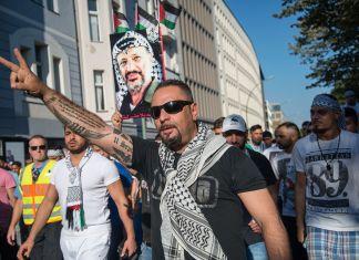 Demonstration in Berlin am 17. Juli 2014: Beim Teilnehmer im Vordergrund ist auf dem Unterarm die von Schwingen umrahmte Zahl achtundachtzig eintätowiert, ein Nazi-Zahlencode für den Hitlergruss. Foto Von Boris Niehaus, CC BY-SA 4.0, https://commons.wikimedia.org/w/index.php?curid=34607239