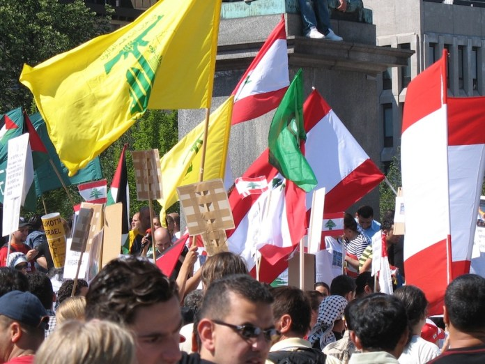 Hisbollah Fahne bei Kundgebung in Stockholm. Foto robotpolisher from Brooklyn, NY, USA - ProtestUploaded by FunkMonk, CC BY-SA 2.0, https://commons.wikimedia.org/w/index.php?curid=14756072