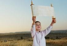 Ein kleiner jüdischer Junge hält eine Thorarolle, vor dem jüdischen Feiertag Schawuot. Foto Flash90