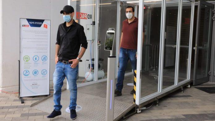Dr. Eran Avraham, links, und Dr. Izaak Cohen von der Bar-Ilan Universität gehen durch den Hygienetunnel am Eingang des Bloomfield-Stadions in Tel Aviv. Foto Yoni Reif.