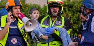 Ein Sanitäter trägt ein verwundetes Kind aus einem Wohnhaus in Ashkelon, das von einer aus dem Gazastreifen abgefeuerten Rakete getroffen wurde, am 11. Mai 2021. Foto Flash90