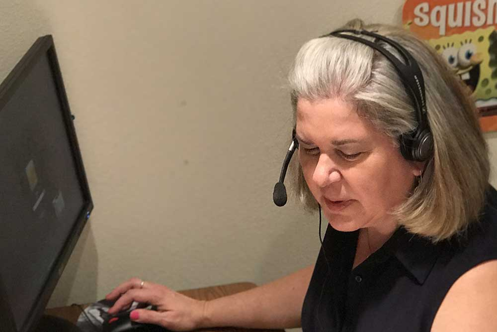 Audiologist Nora working at her desk in the office