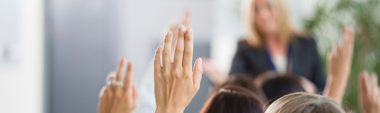 Woman in an audience with her hand raised to ask a question