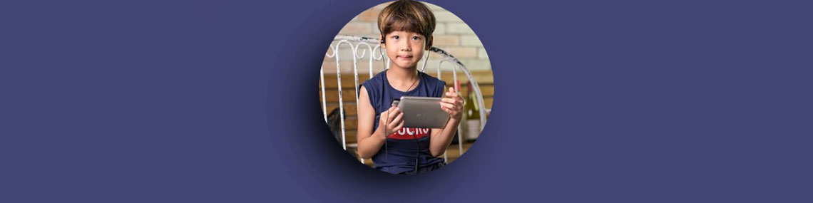 an asian child playing with a tablet device with headphones on