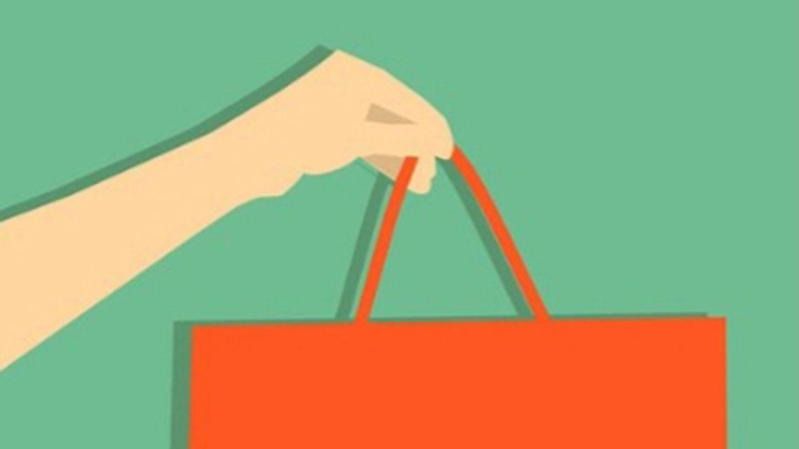 a feminine forearm and hand holding a shopping bag