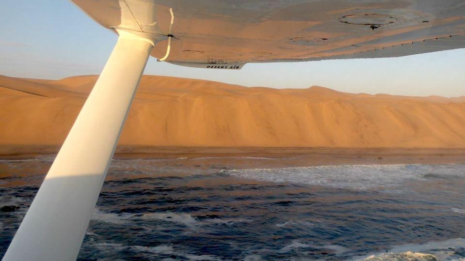 Blick aus der Cessna auf die Wüste und das Meer in Namibia