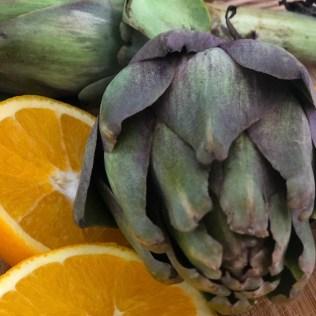 vegetarisches Stilleben mit Orange und Artischocke