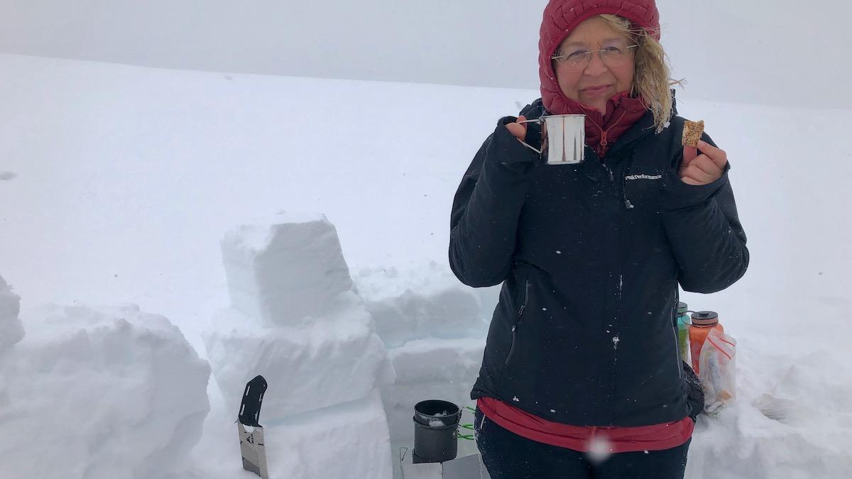 Frau mit Teetasse steht vor einem Iglu