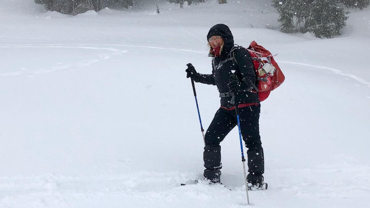 Elke stapft mit Schneeschuhen und Rucksack durch den Schnee.