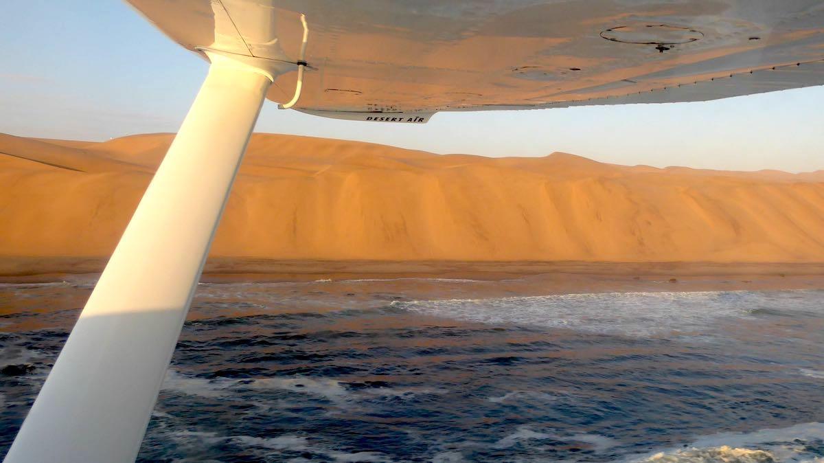 Blick aus einer Cessna über die Wüste Namib und den Atlantik
