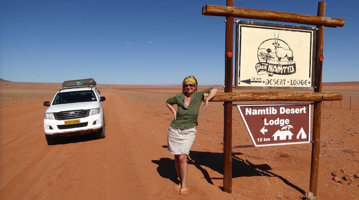 """Elke Zapf steht neben dem Schild zur """"Namtib Desert Lodge""""auf einer roten Sandstraße in Namibia"""
