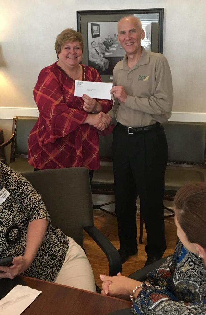 Elaine Mathews gratefully accepts a grant check from Security Federal Bank
