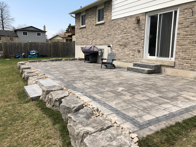 Large interlocking stone patio with natural stone retaining wall and large granite steps