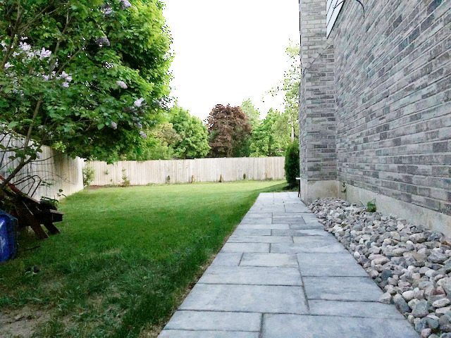 stone path connecting patio and driveway backfilled with medium sized river rock