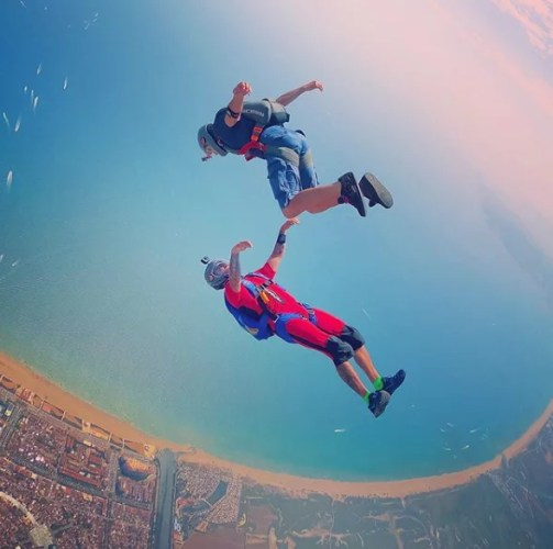Skydivers jumping over Empuriabrava using short jumpsuit