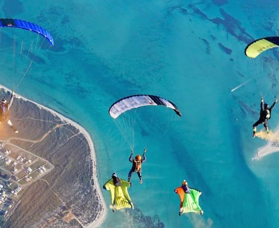 Canopies and wing suit working together during a skydiving jump in Australia