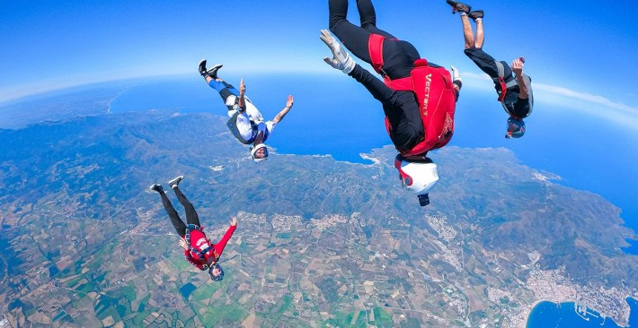 Skydivers flying over the Mediterranean ocean during the Colorful Camp