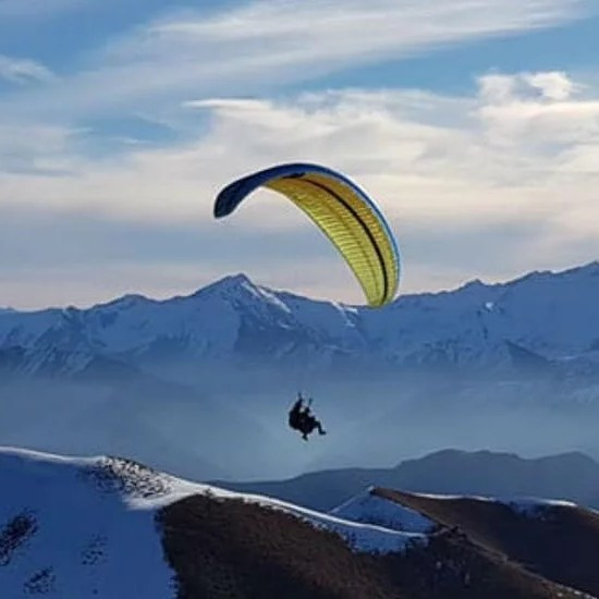 paragliding over mountains with snow