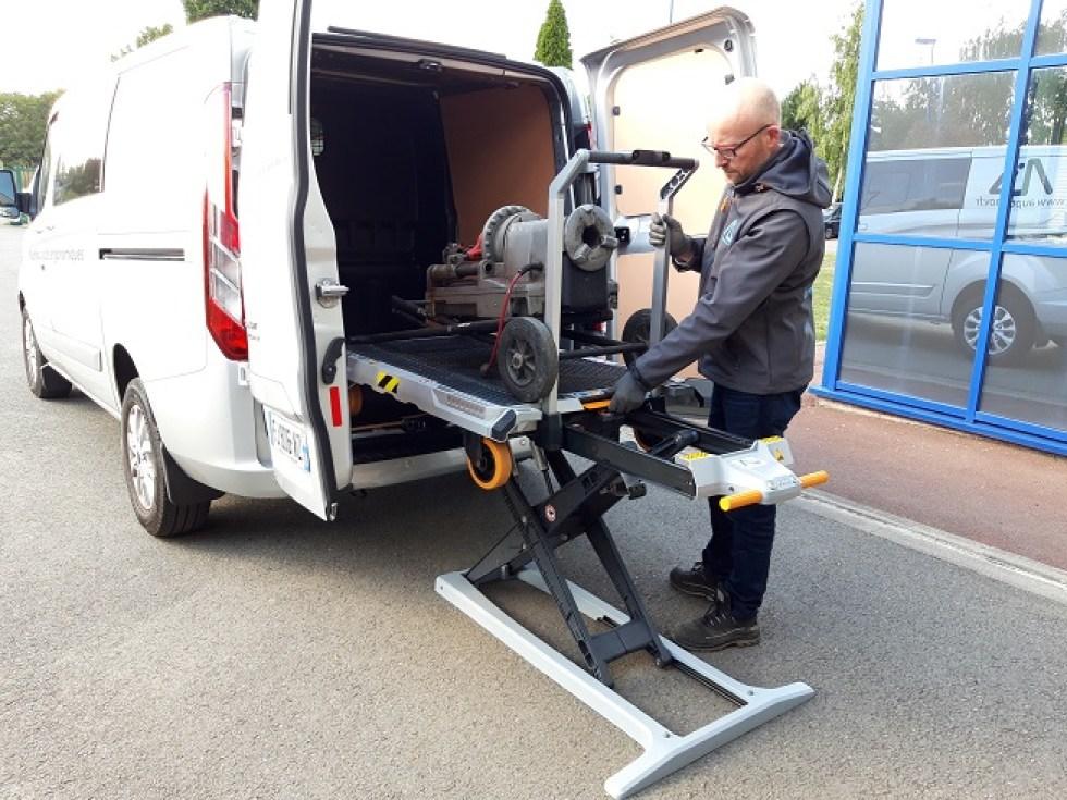 Le chariot est équipé d'une table élévatrice qui permet de mettre le plateau à hauteur et d'un système qui lui permet de s'autochager dans un véhicule sans effort