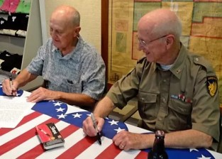 Creator of Andy Aurora, Jerry Morrow and Aurora mayor Al McCoy signing Andy memorabilia in 2012