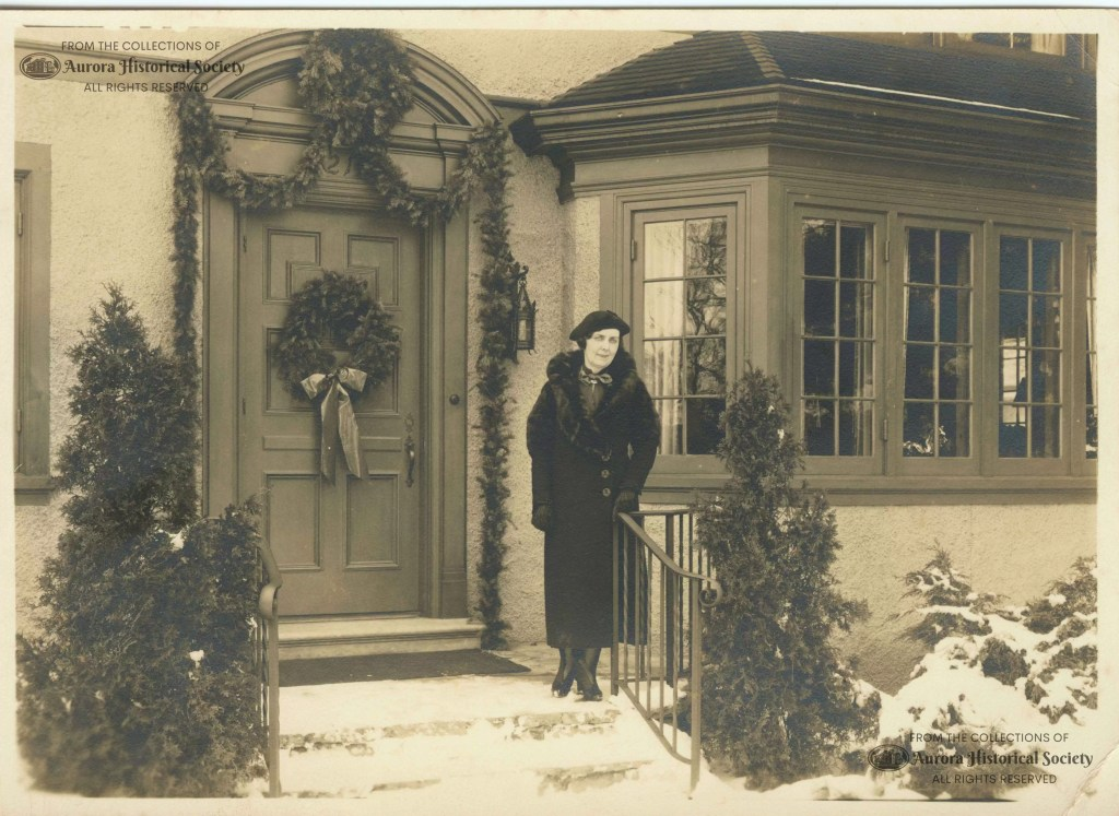 Luella Dude Kendall, wife of Myron Kendall, in front of their decorated home at 1211 Garfield, about 1940 (Aurora Historical Society photo)
