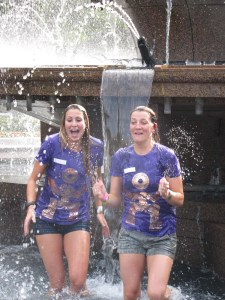 Two girls getting drenched in a fountain