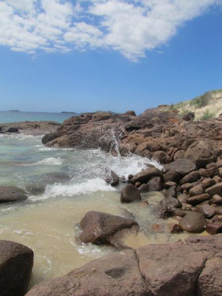 Waves break over a tiny rockpool