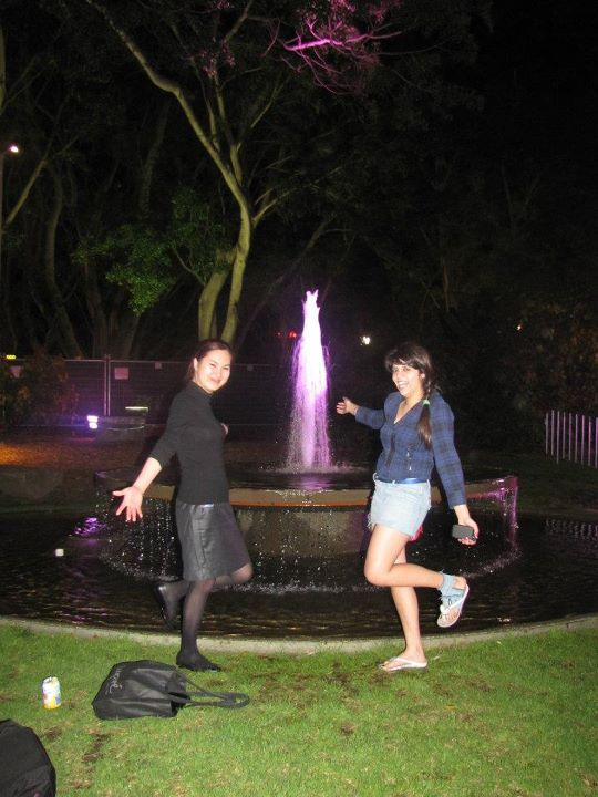 Two girls posing by a fountain