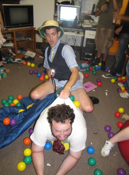A man rides another man in a ball-pit while holding a rifle