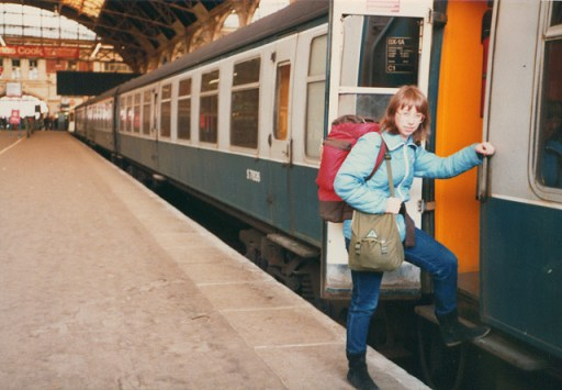 A backpacker boards a train in the 1980s