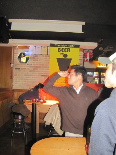 A Korean man plays darts in a bar