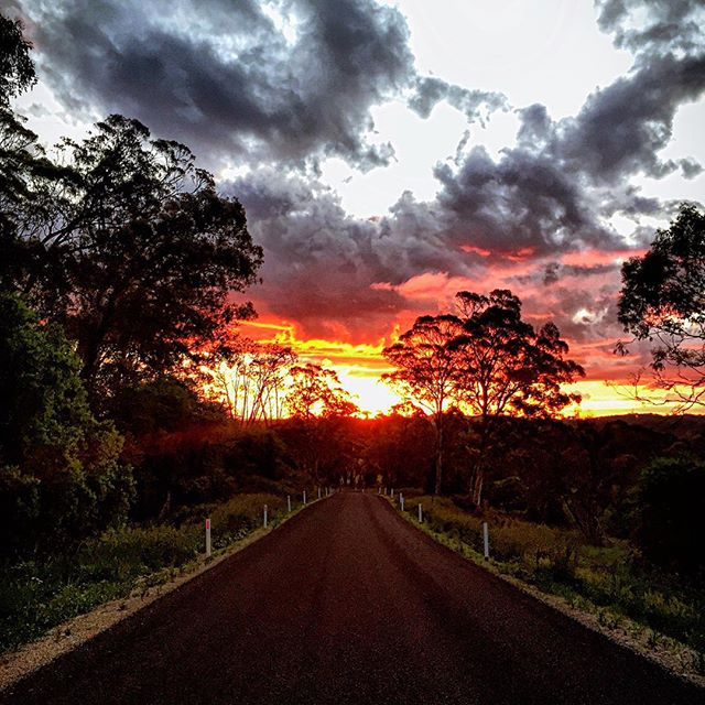 The sun sets over an idyllic country road.