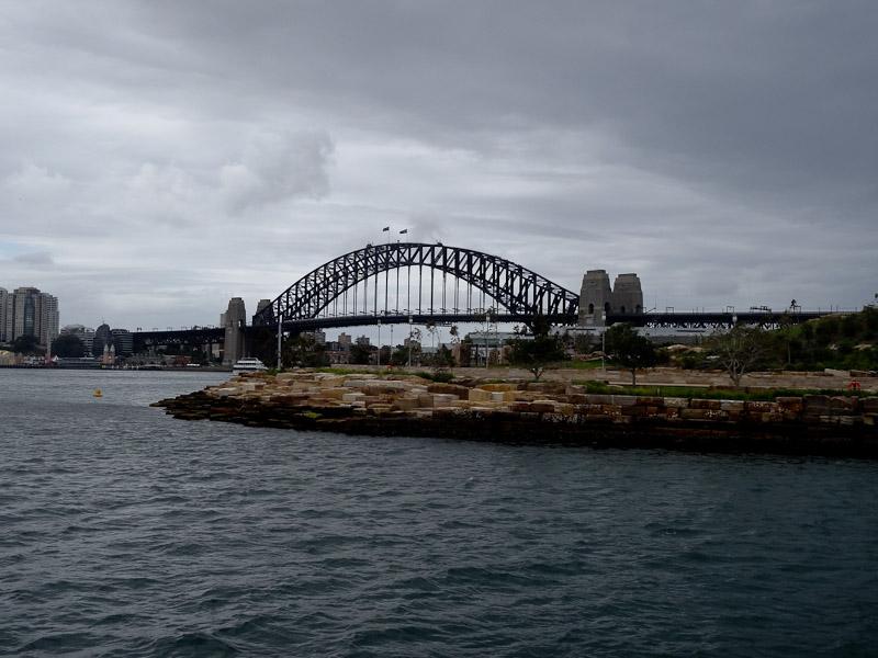 Sydney Harbour Bridge beneath a stormy sky.