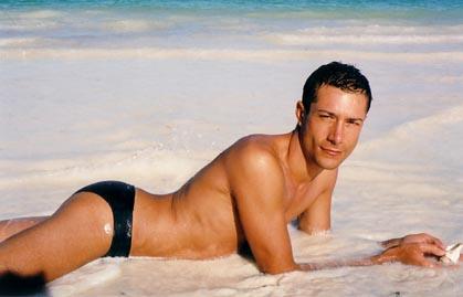 Cute guy on the beach in black speedos.