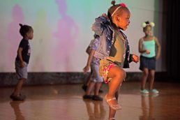 A group of children dance to music on stage last Friday, during the annual Exclusive Spring Fashion Show inside the auditorium at Ella Flagg Young Elementary School in Chicago's Austin neighborhood. | Photos by ALEXA ROGALS/Staff Photographer