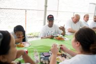 Army veteran Larry McLaughlin eats lunch and talks with the volunteers last Thursday.Volunteers fixed different parts of McLaughlin's home. | By ALEXA ROGALS/Staff Photographer