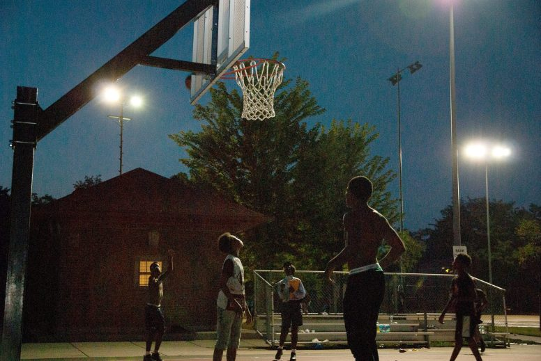 Young men play basketball after National Night Out in Austin, held Aug. 7. | Shanel Romain/Contributor