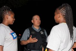 CONNECTIONS: A 15th District police officer speaks to young people who attended the district's National Night Out festivities in Austin on Aug. 7. Even after the festivities ended, young men played basketball well into the night. | Shanel Romain/Contributor | Shanel Romain/Contributor