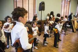 Students playing the violin and cello listen to others play their piece as they wait their turn on Saturday, Dec. 8, 2018, during the Westside Instructional String and Harp Program's Holiday Recital at the Garfield Park Fieldhouse in Chicago. | ALEXA ROGALS/Staff Photographer