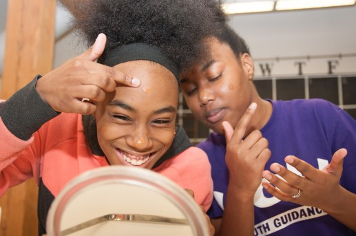 Girls applying makeup at a confidence-building session hosted by Harris in Chicago. | Shanel Romain/Contributor