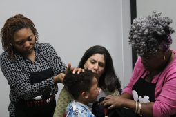 GENTLE TRANSFORMATION: From left: Styles 4 Kidz Founder and Executive Director Tamekia Swint; adopted mom Laura Basi; and hair stylist Lyneshia Franco, attend to Basi's 3-year-old son Steven as he receives hair treatment. | WENDELL HUTSON/Contributor