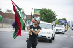 Participants wave flags and celebrate on Saturday, June 15, during the fifth annual African-American Awareness and Appreciation Parade Juneteenth Celebration on Madison Street on Chicago's Westside. | ALEXA ROGALS/Staff Photographer