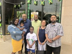 OPEN FOR BUSINESS: Mark Phillips (in the green shirt) opened the Maywood store with his wife Askale, far left. Front row: Askale, daughter Yara, son Jovanni Finley, Eugenia and brother Landon Rowan. Back row: Barrington and Mark. | MICHAEL ROMAIN/Staff