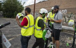 Riders put their helmets on on Wednesday, Aug. 7, in an empty lot on Pulaski Street off of North Avenue in Chicago. | ALEXA ROGALS/Staff Photographer