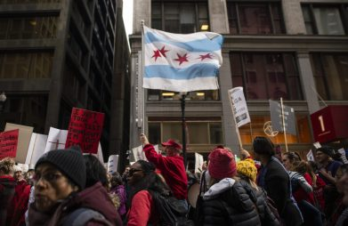 Marchers hold up signs and Chicago city flags on Thursday, Oct. 17, during a Chicago Teachers Union rally in the Chicago Loop. | ALEX ROGALS/Staff Photographer
