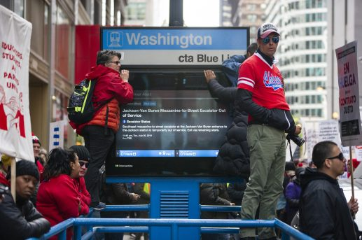 Pedestrians stand near the Washington Blue Line stop to watch the crowd make their way down Dearborn Street on Thursday, Oct. 17, during a Chicago Teachers Union rally in the Chicago Loop. | ALEX ROGALS/Staff Photographer