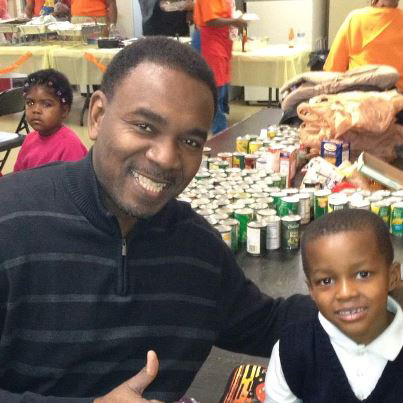 No one has to tell little Corey Coffey how to give back to his community. The 6-year-old student from Austin's St. Angela School, 1332 N. Massasoit, led a Thanksgiving food drive at his school to collect items for Greater St. John Bible Church. (Rev. Ira Acree pictured)