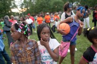 Timya Williams, center, and Jenascia Bell, listen to the closing prayer during National Night Out festivities at Moore Park. (David Pierini/staff photographer)