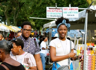 Two youth walk down a path lined with vendors selling a variety of food, clothing, skin care products and art. (ASHLEY LISENBY/digital editor)